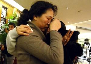 14mar2014---uma-mulher-chora-enquanto-abraca-parente-de-passageiro-do-voo-da-malaysia-airlines-que-esta-desaparecido-apos-receber-novas-informacoes-sobre-o-aviao-em-pequim-na-china-1395260558230_1024x771